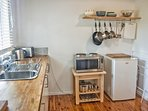 Kitchenette with sink, bar fridge, stove with microwave, convection oven and hotplates
