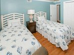 Soothing blue nautical decor in second bedroom with two twins