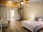 Master bedroom suite with a queen bed and view of the loft above and queen sleeper sofa
