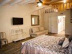 Master bedroom with queen bed, flat screen TV, queen sleeper sofa and 2 twin beds in the upper-level loft