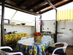 The dining table is next to the cooking and barbeque areas on the main deck