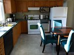 eat in kitchen and large dining room table with lots of appliances, including toaster, kettle, etc