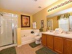 The 1st floor master ensuite bathroom with sunken bath, shower & double sink