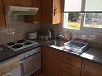 Kitchen with washing machine, dishwasher, kettle, toaster, microwave.