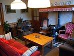 Woonkeuken met comfortabele fauteuils en een bank. Heerlijk zitten rond de potkachel.