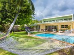 The ultra-private back yard comes with a pool, hammock, lawn chairs, and barbecue.