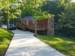 Uniquely hand crafted cedar cabin with concrete driveway for cars and motorcycles.