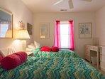 Guest bedroom with 2 twin beds, dresser, desk, nightstand, TV, closet.