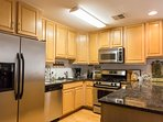 Well-stocked kitchen with Modern stainless steel appliances, microwave, coffee maker, toaster & more