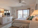 Master bedroom with king-size bed and balcony with bay view.