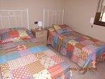 dormitorio con dos camas individuales de 90 cada una, ventana con vistas al jardin