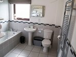 Large bathroom, bath with overhead shower. Luxury toiletries, fluffy towels and bathrobes.