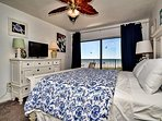 King size bed, flat screen TV and balcony access in the master bedroom.