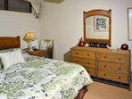 The bedroom offers a queen bed and plenty of storage space