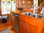 An island houses a deep double sink and dishwasher