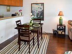 The unit is decorated in a breezy tropical style and features lovely original oil paintings
