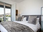 Bedroom One with views of the city and outside balcony