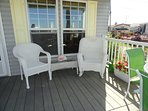 Deck furnished with  wicker chairs, table and  chairs, gas grill below deck