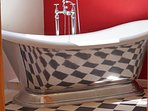 Polished aluminium boat type bath with shower mixer taps.