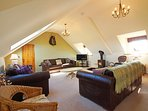 Upstairs living with 2nd TV, large leather suite and a log burner.
