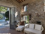 Outdoor lobby with open doors towards the pool and 100 years old olive trees in courtyard