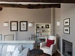 indoor living on 2nd floor with wing chairs, a little librery and an open fire place
