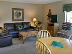 Beaver Creek West Condo F-2 living room with sofa bed, wood fireplace, dining table, and balcony w/