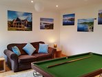 Games room with pool table, sofa bed and children's toys. Aerial photographs of area on display