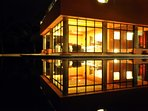 House at night reflected in the pool.
