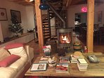 Open plan living area with modern wood burner, sitting and dining areas