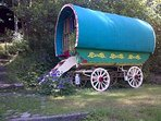 The wagon, canopied by trees and settled by the stream.