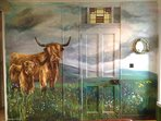 The house is very unique, with painted wildlife. Here in the lounge Highland cows cover the wall.