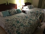 Guest bedroom with 2 queen size beds and  a flat HDTV