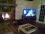 Wood burning fireplace in front of sectional sleeper sofa, surround stereo system and 4k tv.