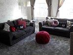 Large lounge with 2 large sofas and huge sash windows