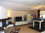 Wohnzimmer mit offenem Kamin und großzügigem Essbereich für 6 Personen