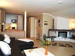 Wohnzimmer mit offenem Kamin und offener Küche