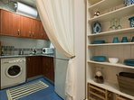 Adjacent to the living area, separated by a curtain, is the small kitchen.