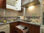 Kitchen with washing machine, stove-top, fridge/freezer, microwave and cooking utensils.