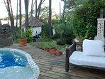 Al lado de la piscina, sofa con mesa baja mas reposeras de teca. Ducha al aire libre.