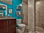 bunk room bath has walk-in travertine shower with teak stool