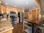 modern kitchen with stainless appliances, stainless rolling island, maple wood eating bar