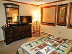 Roomy master bedroom features flatscreen TV and spacious dresser