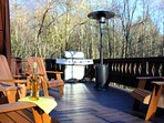 Sit On The Deck On The Adirondack Chairs With Two Outdoor Heaters