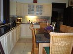 Second kitchen with granite top table and chairs.  All cooking utensils and cutlery