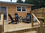Back deck with propane fire pit and barbecue.