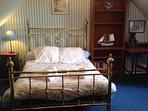 First floor. Bedroom 3: Carpeted double bedroom with garden views.