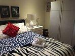 Bedroom 1: Queen bed and wardrobe