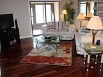 Spacious living room with vaulted ceiling, wood floors, couch, loveseat, flat screen TV and DVD player.  Sliders to the...
