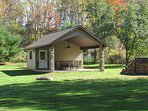 Covered Pavilion w/ Storage of Outdoor Accessories including Kayaks and Lawn Chairs.